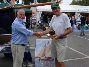 "Mike came to the Honnor Marine stand at the Southampton Boat show in September 2009 with his trophies from the race, a plate and a trophy made from a dead eye block from Shackleton's ""Endurance"". Here he is with Bob, next to the Cape Cutter 19 show boat."